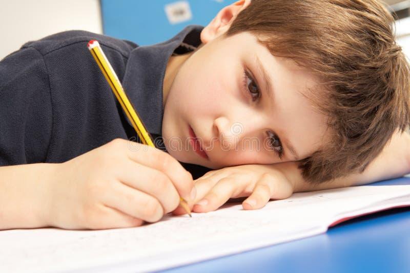Écolier malheureux étudiant dans la salle de classe photographie stock libre de droits