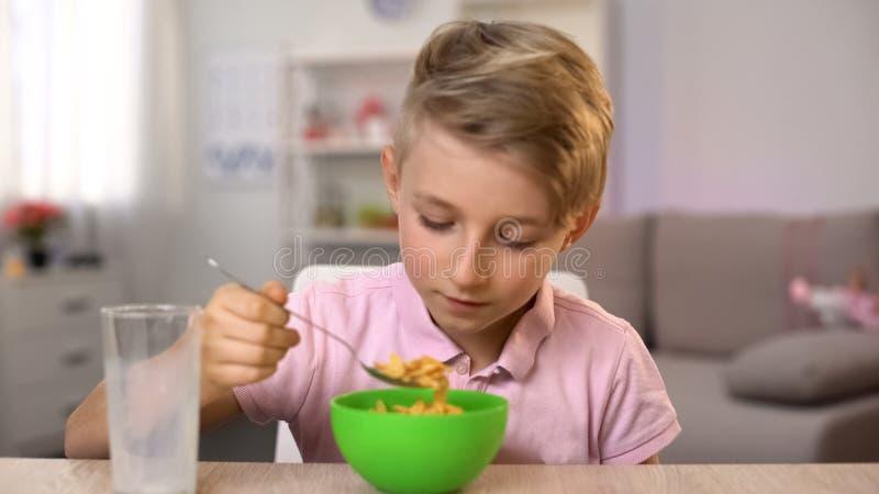 Écolier mangeant des cornflakes avec du lait pour le petit déjeuner, nutrition saine, suivant un régime images stock