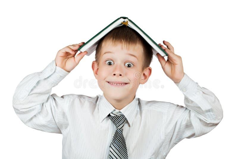 Écolier mignon avec un livre sur sa tête. d'isolement image stock