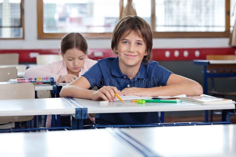 Écolier mignon s'asseyant dans la salle de classe photographie stock libre de droits
