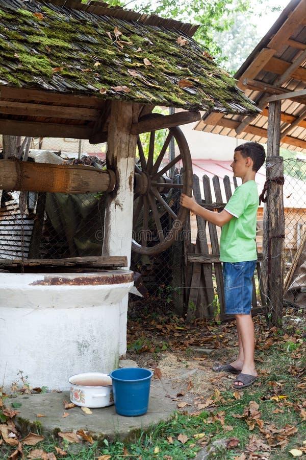 Écolier obtenant l'eau du puits photographie stock libre de droits