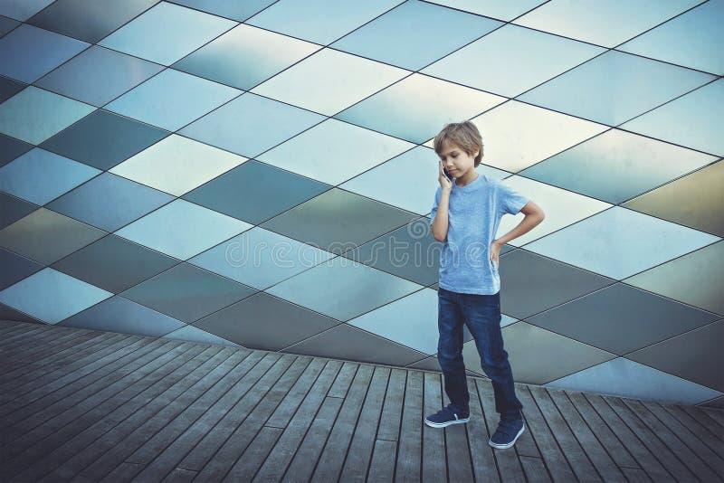 Écolier parlant au téléphone dans la ville images libres de droits
