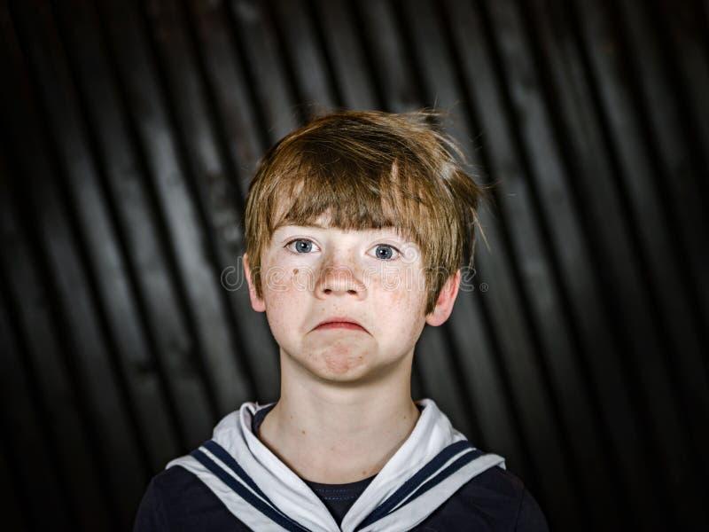 Écolier posant dans le costume de marin avec des émotions photo libre de droits