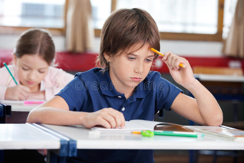 Écolier réfléchi s'asseyant au bureau image stock
