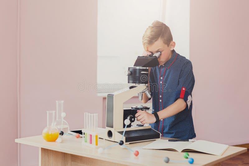 Écolier regardant dans le microscope sur la leçon photographie stock