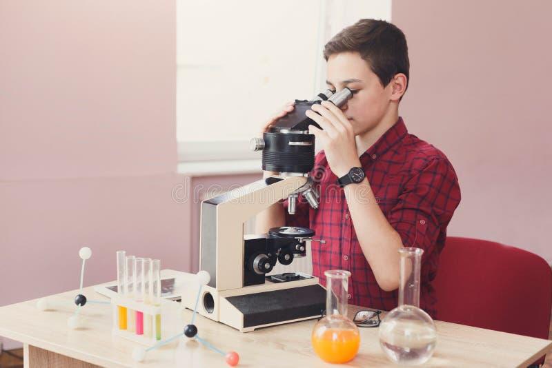 Écolier regardant dans le microscope sur la leçon images stock