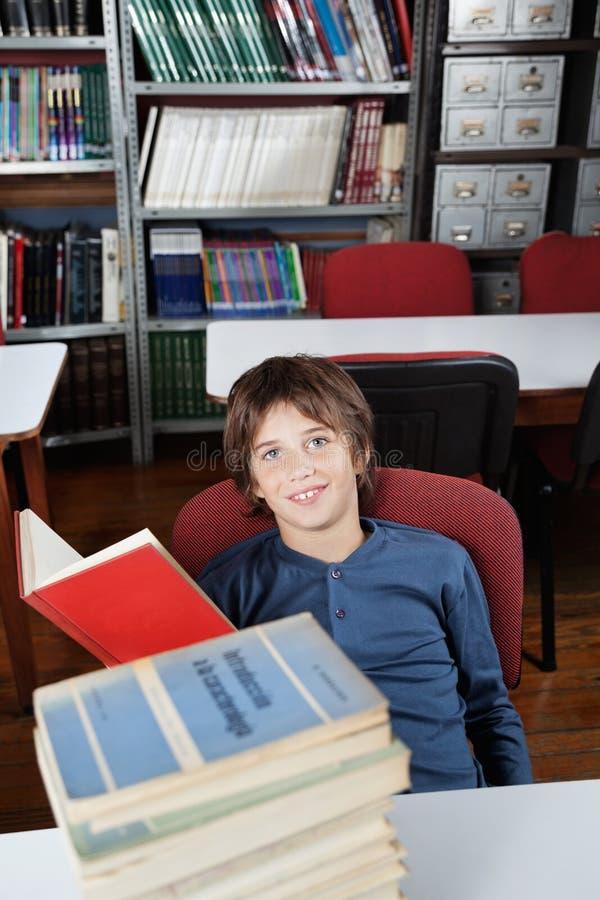 Écolier s'asseyant avec les livres empilés au Tableau images stock