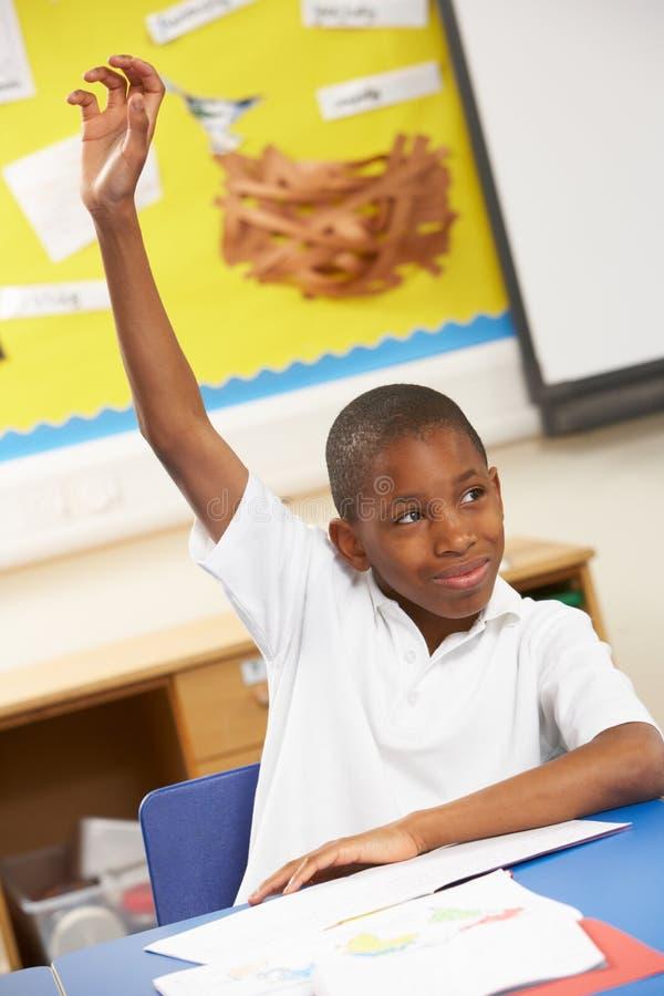 Écolier soulevant la main dans la salle de classe photo stock