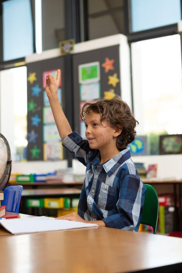 Écolier soulevant sa main au bureau dans la salle de classe photographie stock libre de droits