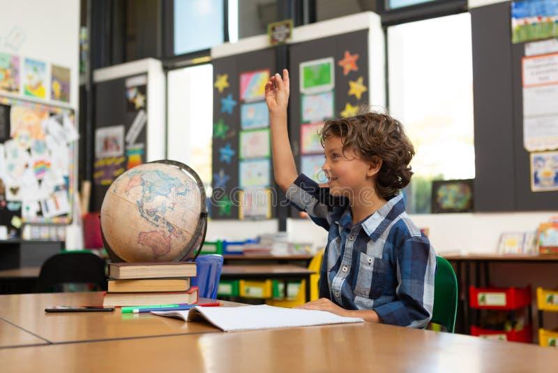 Écolier soulevant sa main au bureau dans la salle de classe photos stock