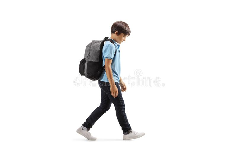 Écolier triste marchant avec sa main vers le bas image stock
