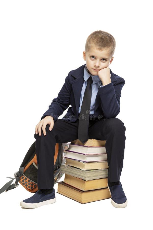Écolier triste mignon s'asseyant sur une pile de livres D'isolement sur un fond blanc image libre de droits