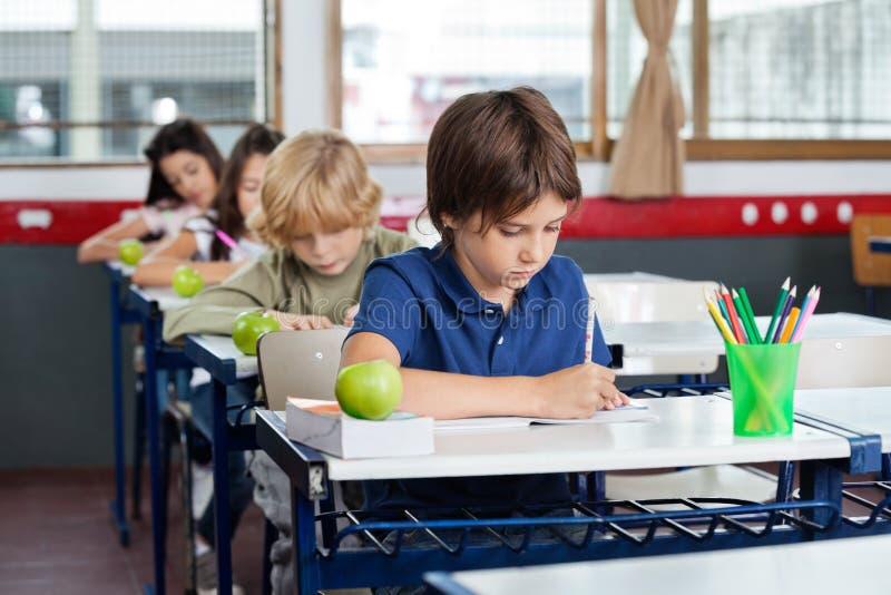 Écoliers écrivant dans les livres au bureau photos stock