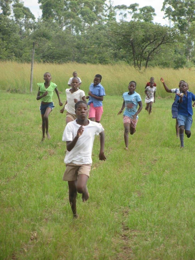 Écoliers aux pieds nus concurrençant dans un événement de voie photo stock