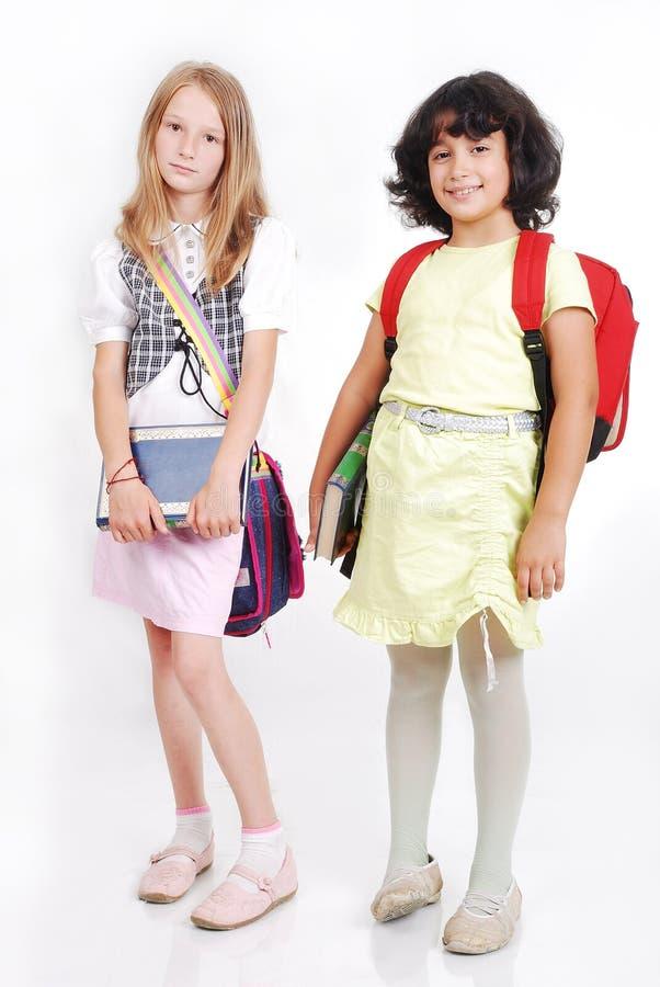 Écoliers avec des sacs et livres d'isolement photographie stock