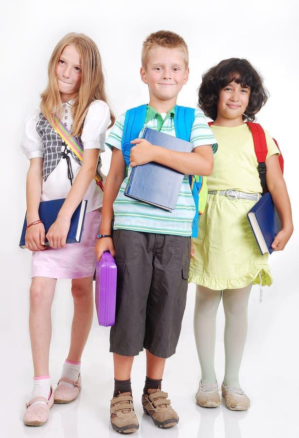 Écoliers avec des sacs et livres d'isolement photographie stock libre de droits