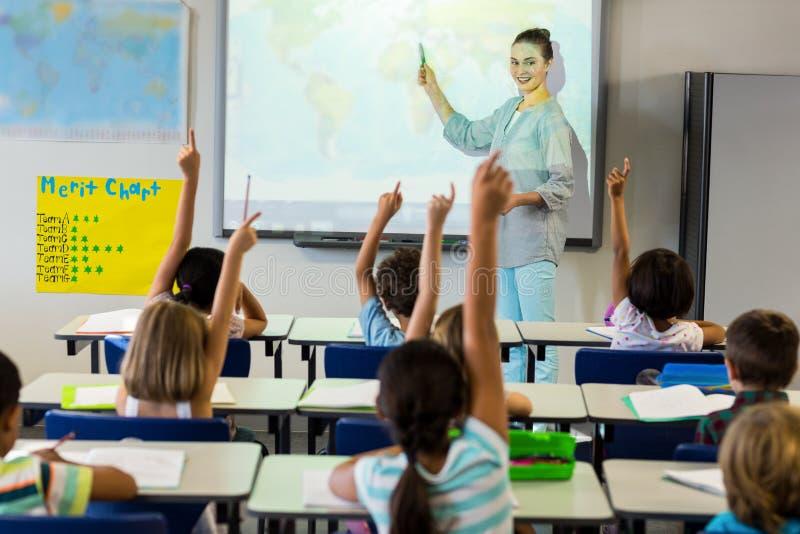 Écoliers de enseignement de professeur à l'aide de l'écran de projecteur photos libres de droits