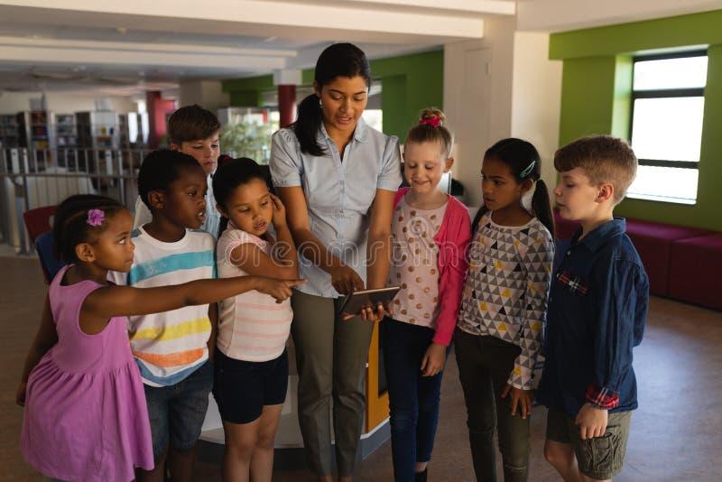 Écoliers de enseignement de professeur féminin sur le comprimé numérique à l'école photographie stock libre de droits