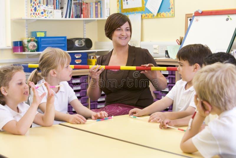 Écoliers et leur professeur dans la classe images stock