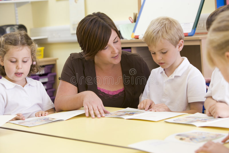 Écoliers et leur relevé de professeur dans la classe photographie stock libre de droits