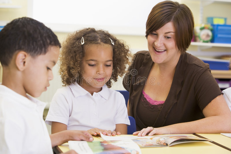 Écoliers et leur relevé de professeur dans la classe images libres de droits