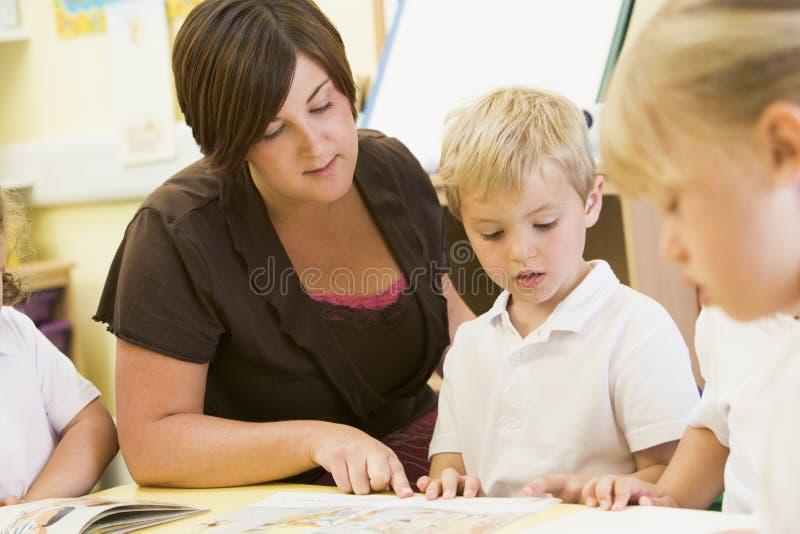 Écoliers et leur relevé de professeur dans la classe images stock