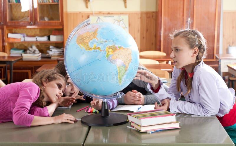 Écoliers explorant le globe dans la salle de classe photo stock