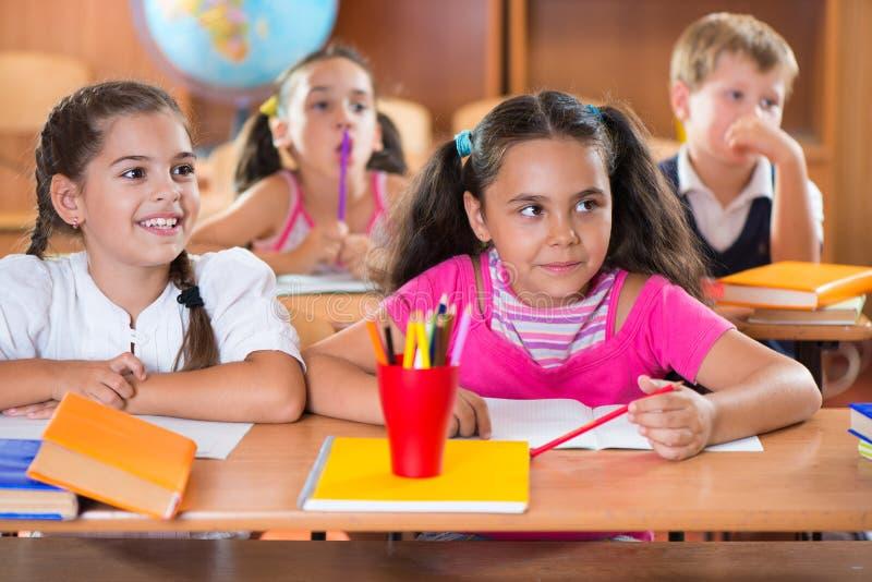 Écoliers heureux pendant la leçon dans la salle de classe photos libres de droits