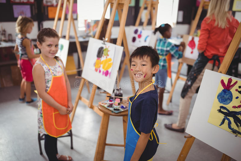 Écoliers heureux pratiquant le dessin photographie stock libre de droits