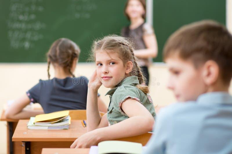 Écoliers heureux s'asseyant au bureau, salle de classe images libres de droits