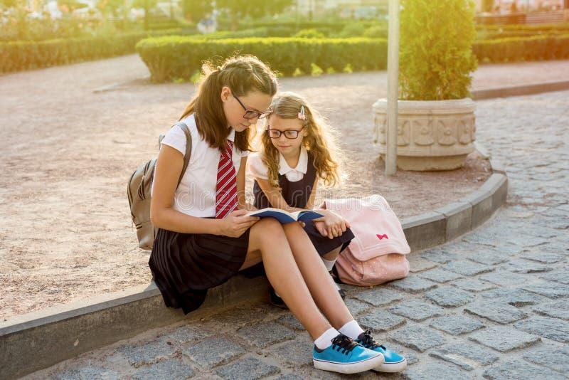 Écoliers lisant un livre se reposant sur le trottoir photo stock