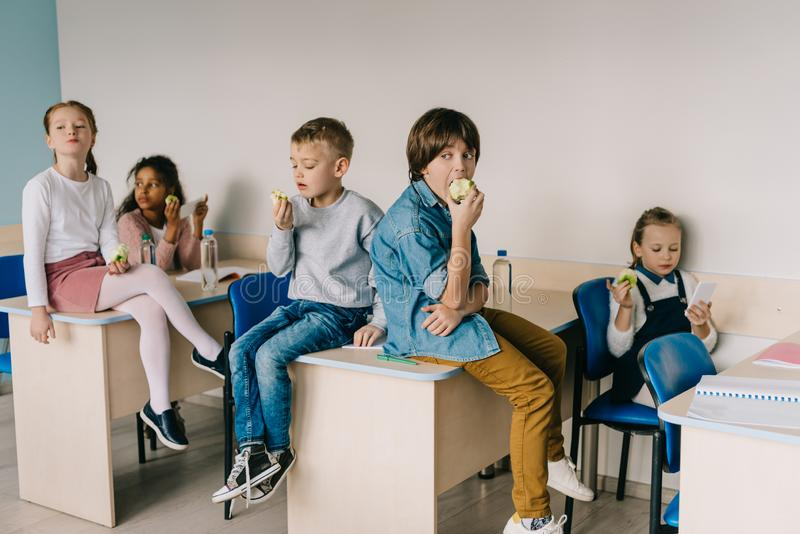 écoliers mangeant des pommes au moment de salle de classe photo stock