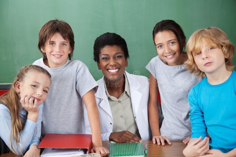 Écoliers mignons avec le professeur féminin At Desk photographie stock libre de droits
