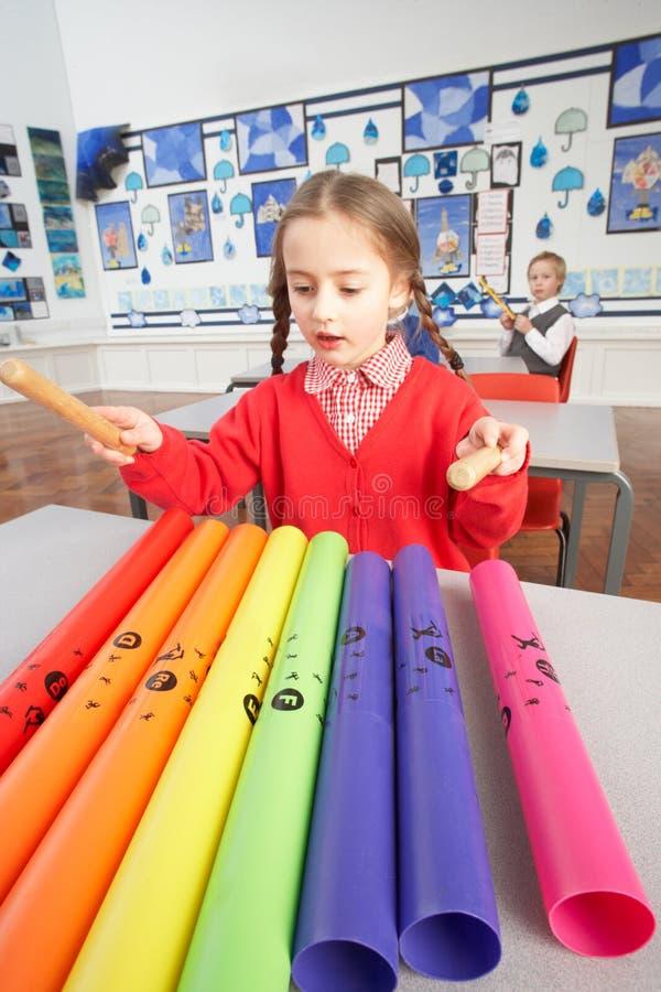 Écoliers primaires ayant la leçon de musique photos libres de droits