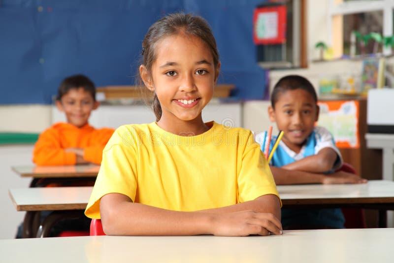 Écoliers primaires s'asseyant aux bureaux dans la classe images libres de droits