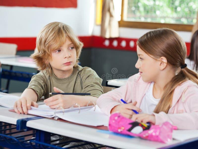 Écoliers regardant l'un l'autre dans la salle de classe photographie stock