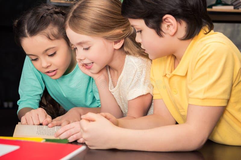 Écoliers se penchant à la table et au livre de lecture ensemble photo stock