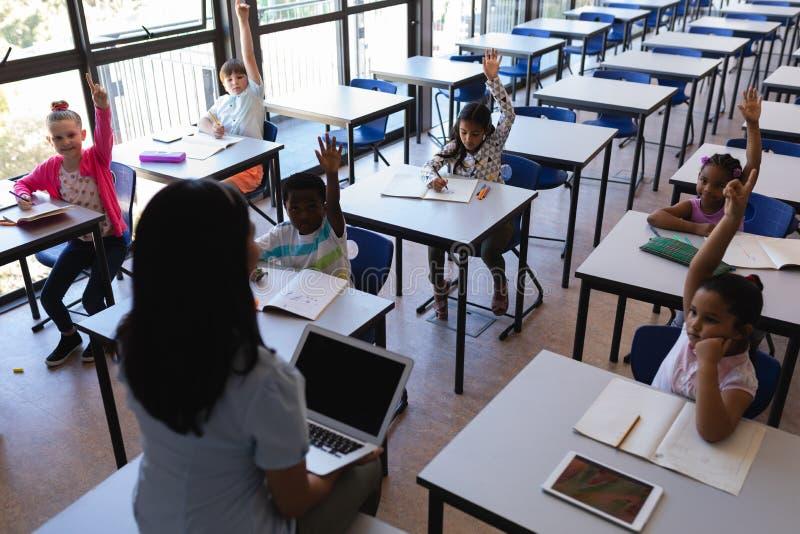 Écoliers soulevant des mains tout en se reposant au bureau dans la salle de classe images stock