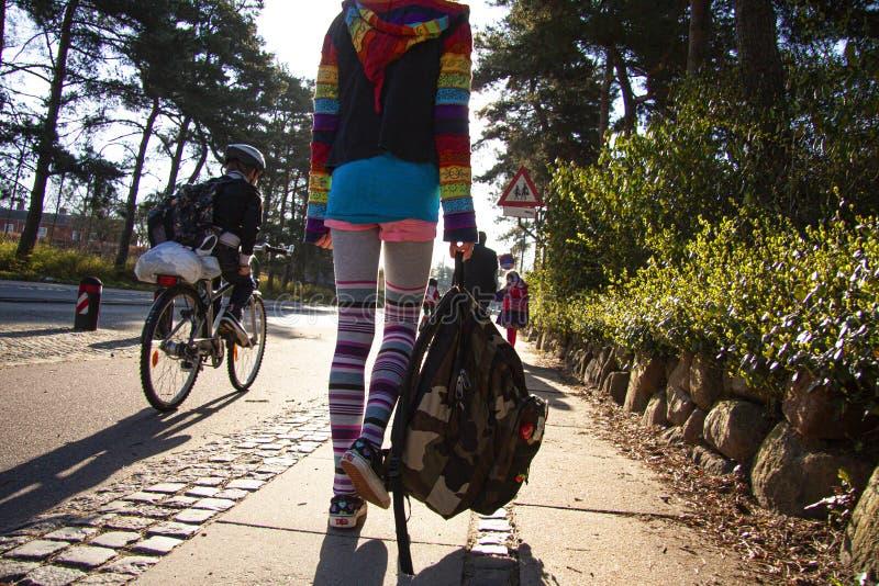 Écoliers sur leur chemin d'instruire pendant le matin marchant et faisant du vélo De nouveau à l'école - image image libre de droits