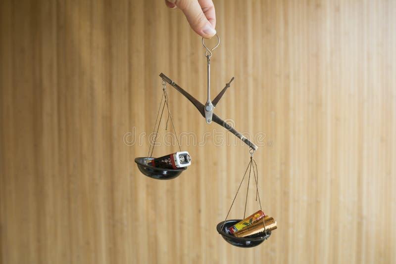 Écologique, réutilisant le concept Différentes batteries dans la Balance photographie stock