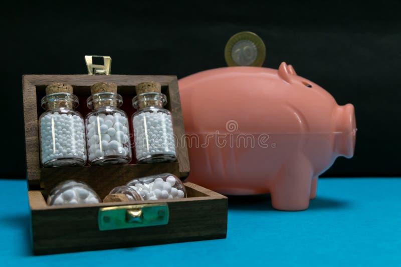 Économie d'argent avec Hopeopathy - bouteilles de médecine homéopathique dans la vieille boîte en bois ouverte et de pièce de mon photos libres de droits