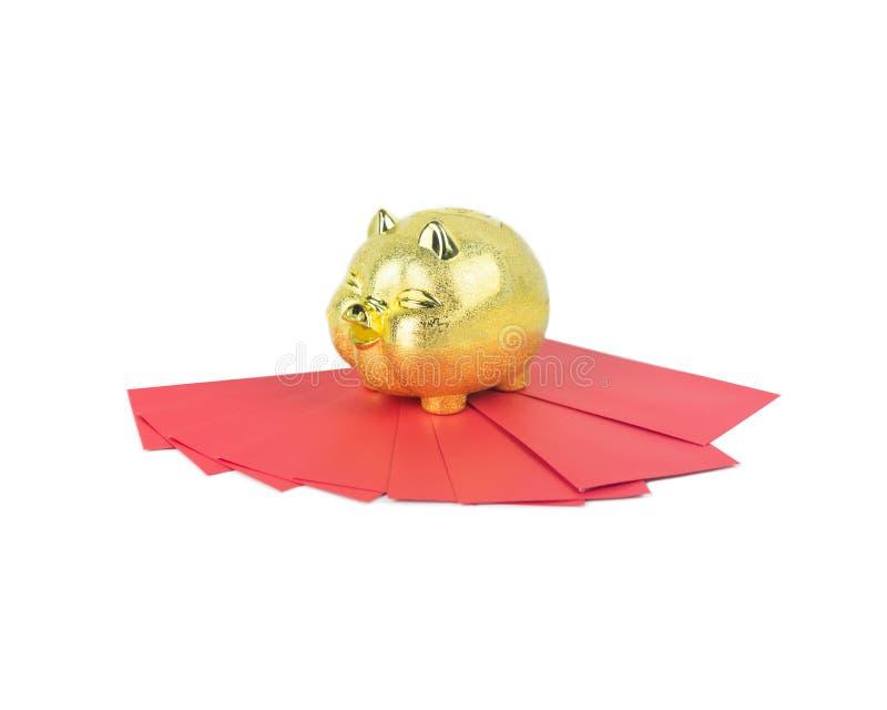 Économie d'or porcine avec l'enveloppe rouge sur le fond blanc d'isolement photo libre de droits