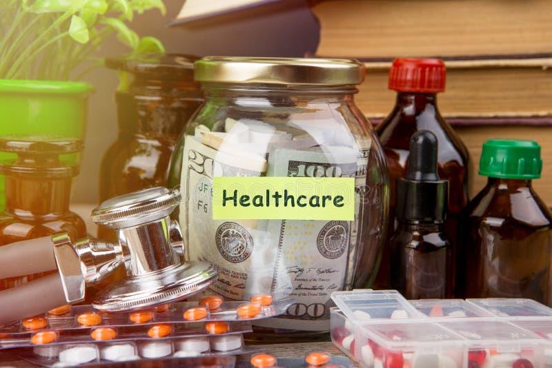 Économiser de l'argent pour l'assurance maladie - verre d'argent, stéthoscope, pilules et bouteilles image stock
