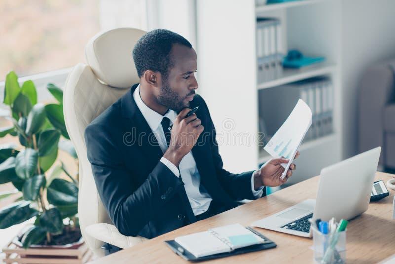 Économiste assidu s'asseyant au bureau dans le poste de travail, endroit, photo libre de droits