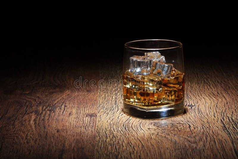 Écossais dans le culbuteur en verre avec des roches de glace sur la vieille surface en bois photos stock