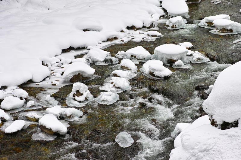 Écoulement de crique dans la neige photographie stock