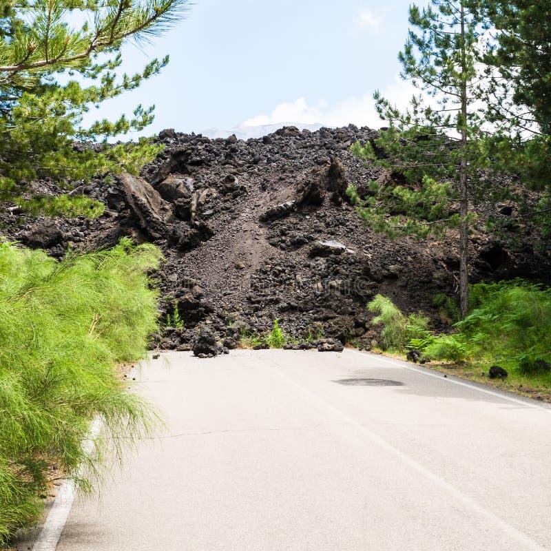 Écoulement de lave durci sur la route sur la pente de l'Etna photographie stock libre de droits