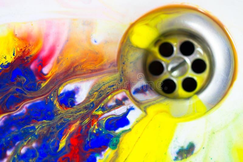 Écoulement multicolore liquide de peinture dans le drain d'évier, concept de créativité images libres de droits