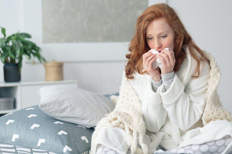 Écoulement nasal de soufflement de femme malheureuse images stock