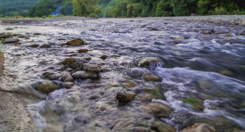 Écoulement rapide d'une rivière de montagne sur un fond d'une forêt verte images libres de droits